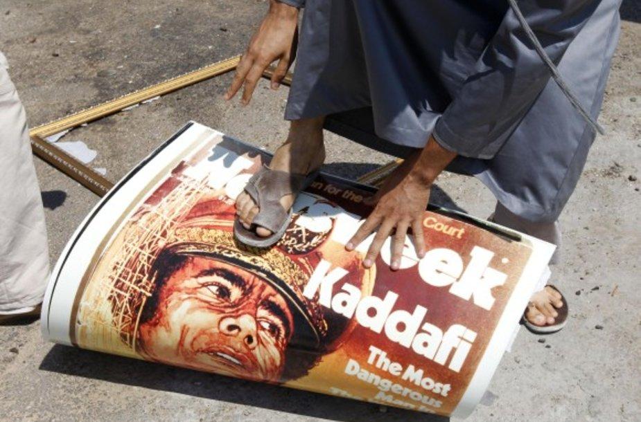 Tripolio gyventojas mindo Muamaro Kadhafi portretą.