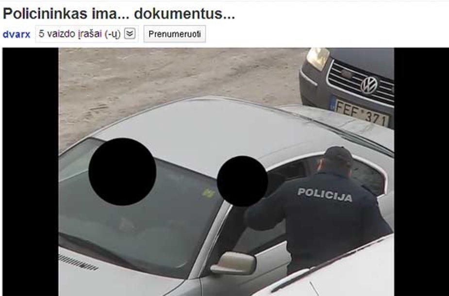 Policininkas tikrina BMW vairuotojo dokumentus