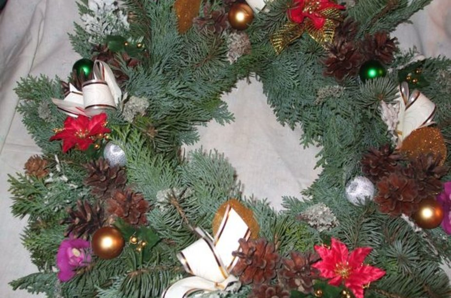 Karštais klijais Dalia priklijuoja kankorėžius, lapelius, įvairias išardytas kalėdines dekoracijas.