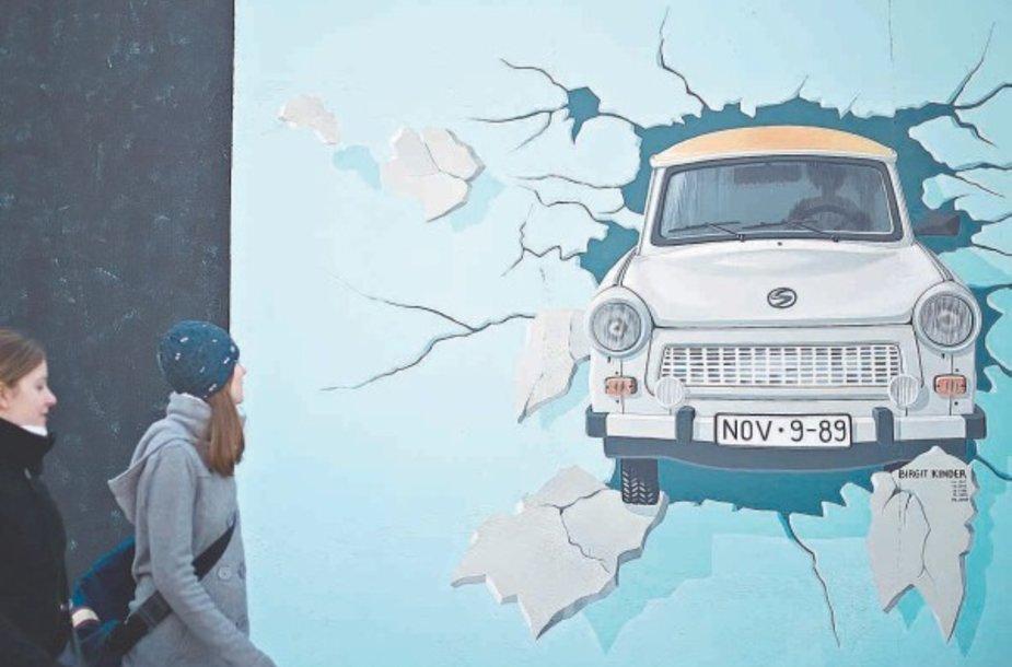 """Turistai ir praeiviai tyrinėja meno kūrinius ant atrestauruotos 1,3 km ilgio sienos ruožo, vadinamo Rytų galerija – sieną pramuša VDR simboliu tapęs automobilis """"Trabant""""."""