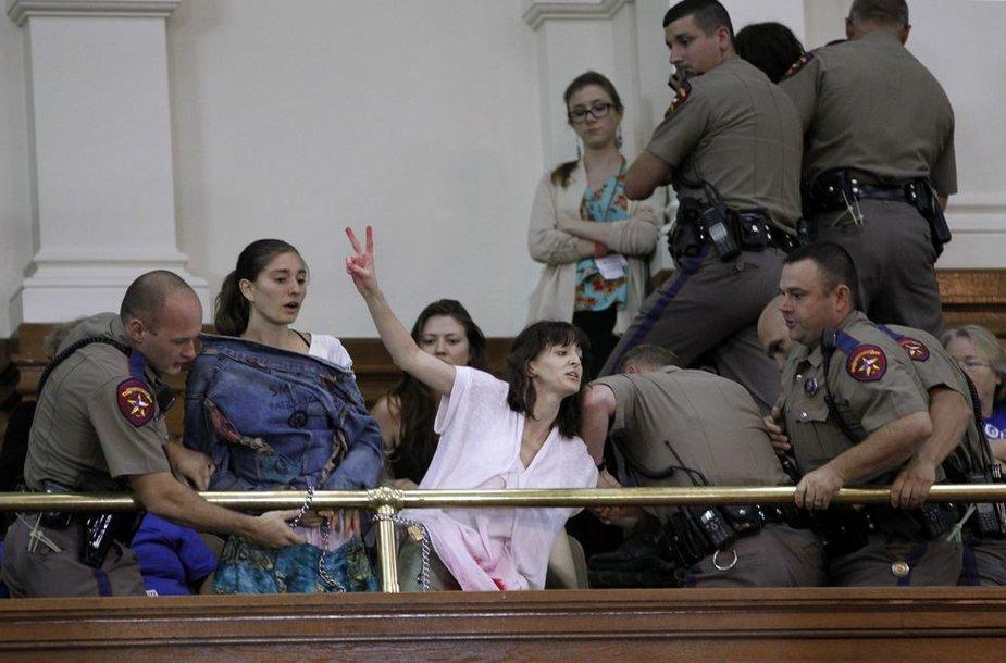 Policininkai mėgina išvesti protestuotojas.