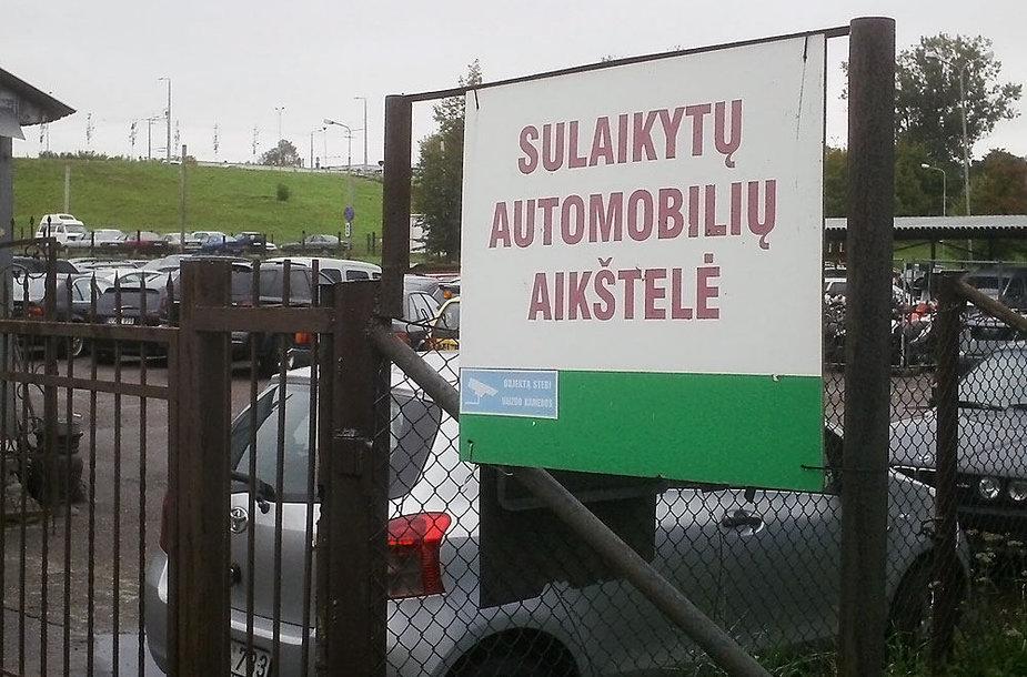 Sulaikytas automobilis stovi iš karto už tvoros