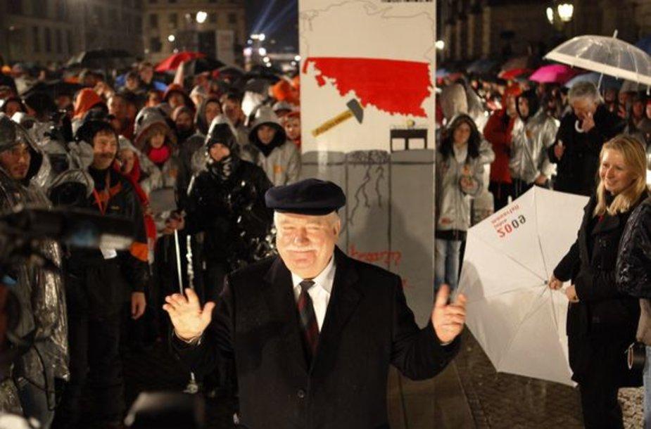 Lechas Walesa prieš stumdamas simbolinę sieną