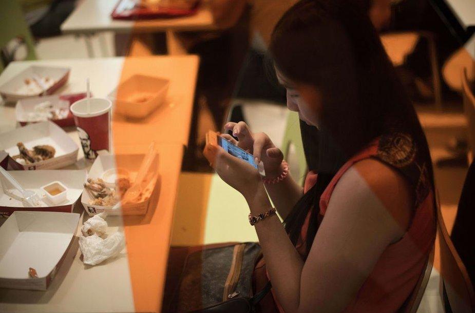 Moteris naudojasi telefonu