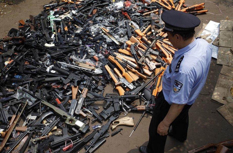 Policininkas prie sunaikinimui paruoštų ginklų