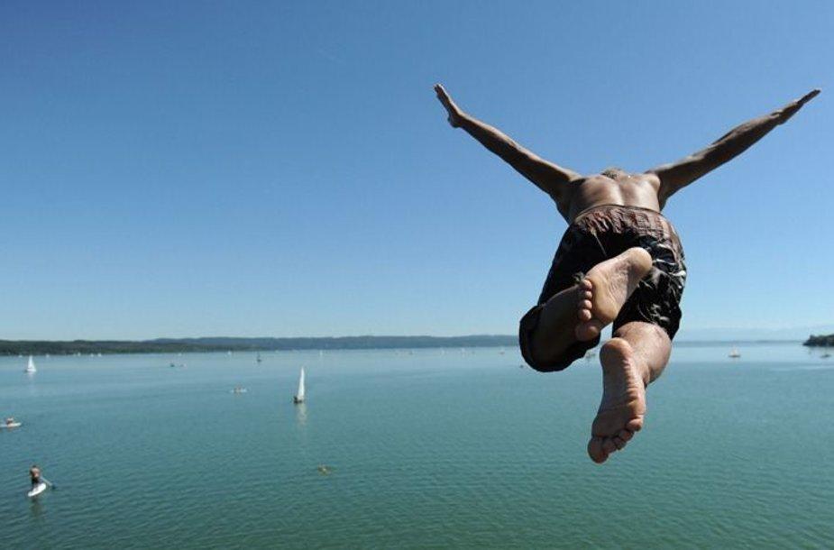 Vyras šoka į vandenį.