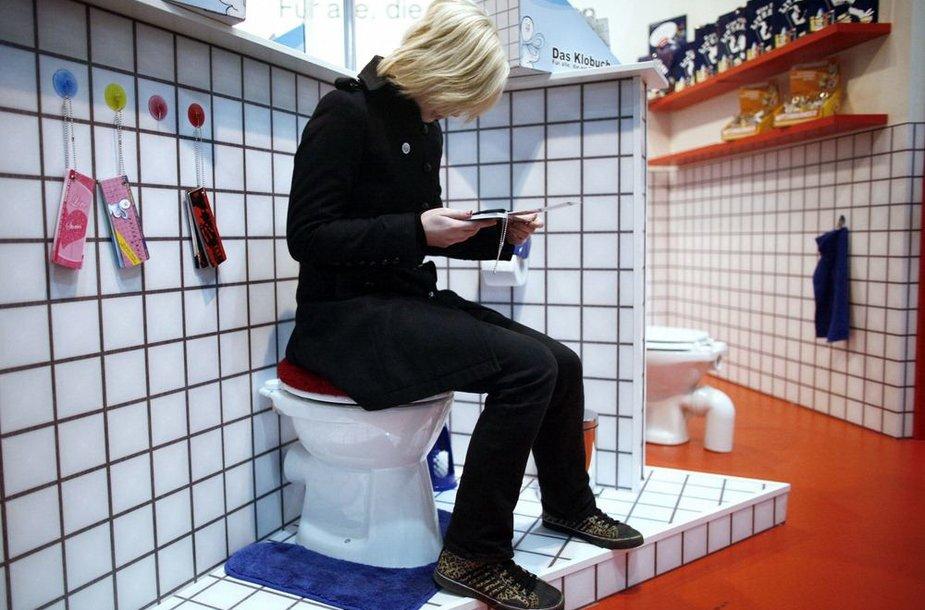 Parodoje moteris skaito lankstinunką sėdėdama ant tualeto