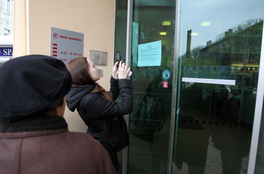 Mergina fotografuoja ant Ūkio banko durų priklijuotą pranešimą.