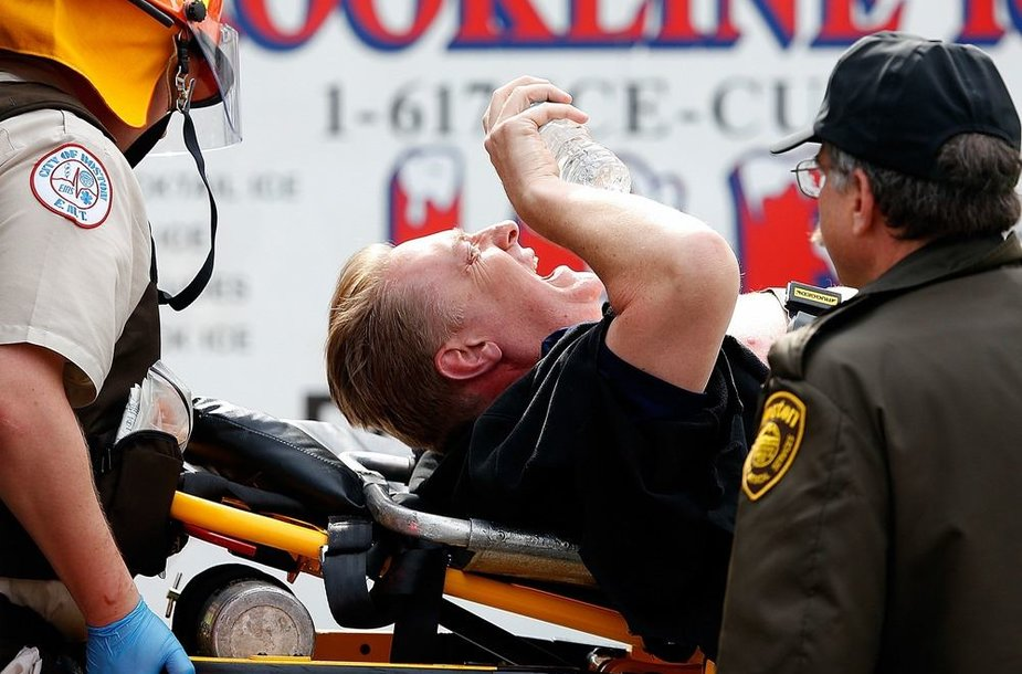 Į greitosios pagalbos automobilį nešamas sužeistas vyras