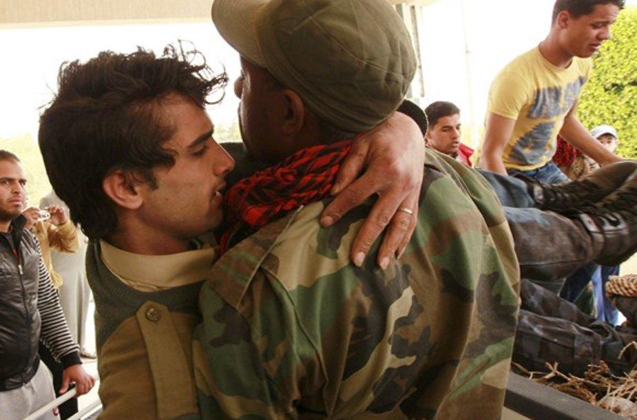 Libijos sukilėlis neša sužeistą kolegą.