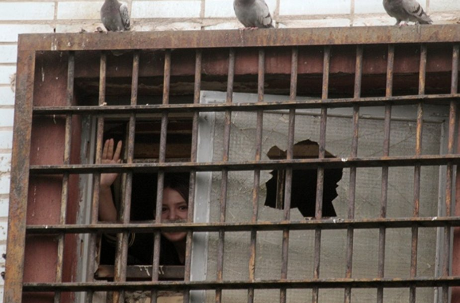 Mergina mojuoja pro kalėjimo grotas Minske.