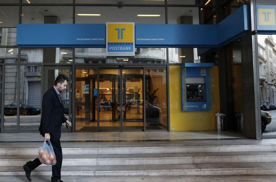 """Žmogus eina pro """"Hellenic Postbank"""" banką Atėnuose"""