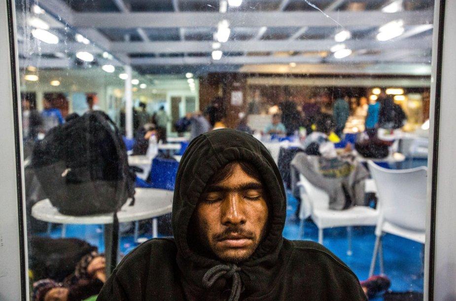 Migrantai miega kelte, plaukiančiame į Atėnus.