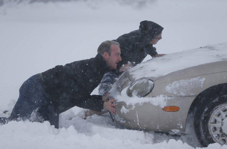 Stumiamas sniegę užklimpęs automobilis