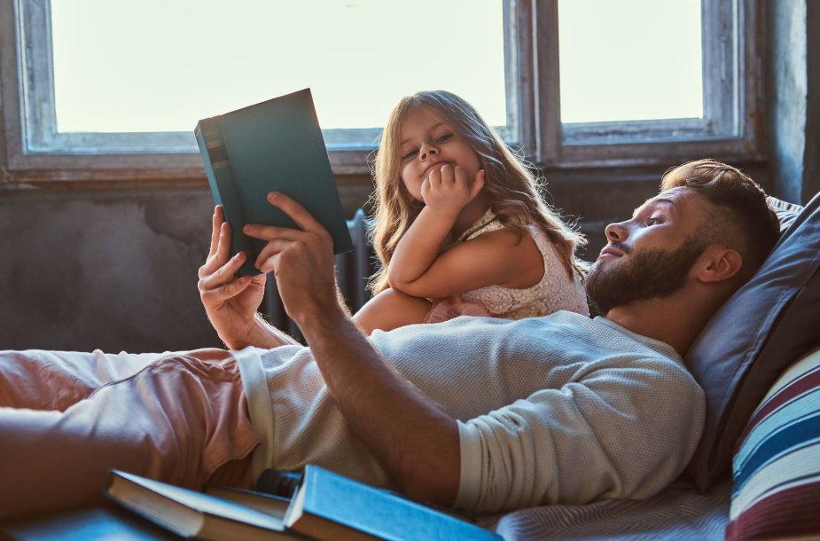 Tėtis skaito knygą dukrai