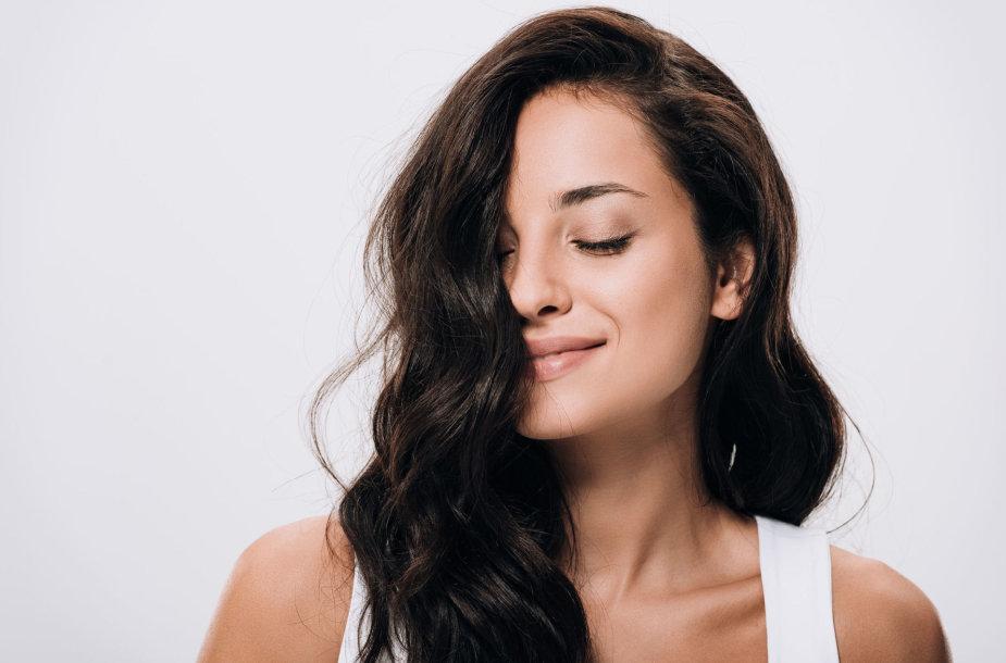 Moteris ilgais banguotais plaukais