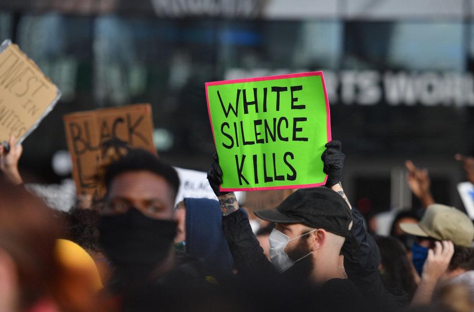 """""""Baltųjų tyla žudo"""" - užrašas ant plakato proteste po George'o Floydo nužudymo"""