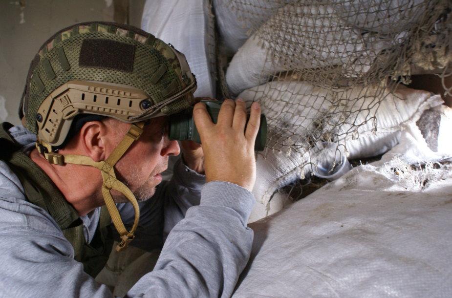 J.Ohmanas per žiūronus stebi už kelių šimtų metrų esančias Rusijos karių pozicijas