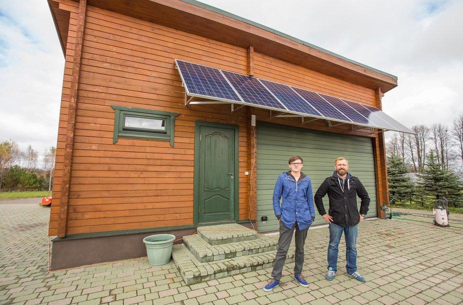 """Prietaiso kūrėjai - UAB ,,Saulės grąža\"""" vadovai, Tomas Šimanauskas ir Žydrūnas Zalieckas, prie Vilniaus raj. nuosavame name įrengtų saulės baterijų su ,,Nectar Sun"""" sistema."""