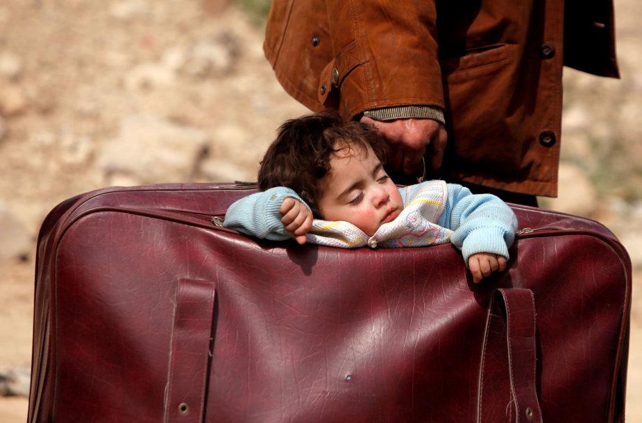 Sirija, 2018 kovo 15 d. Iš šalies bėgančių žmonių vaikas miega lagamine