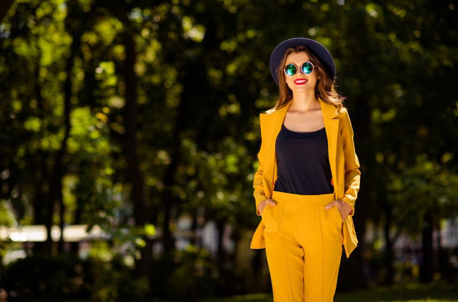 Mergina dėvi ryškų garstyčių spalvos kostiumą