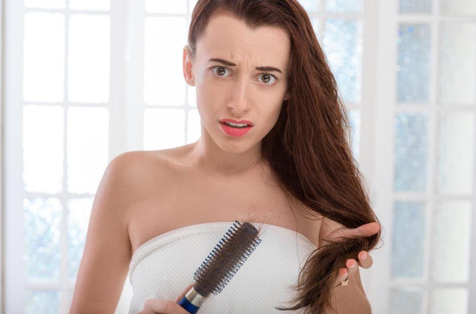 Moteris susirūpinusi plaukais