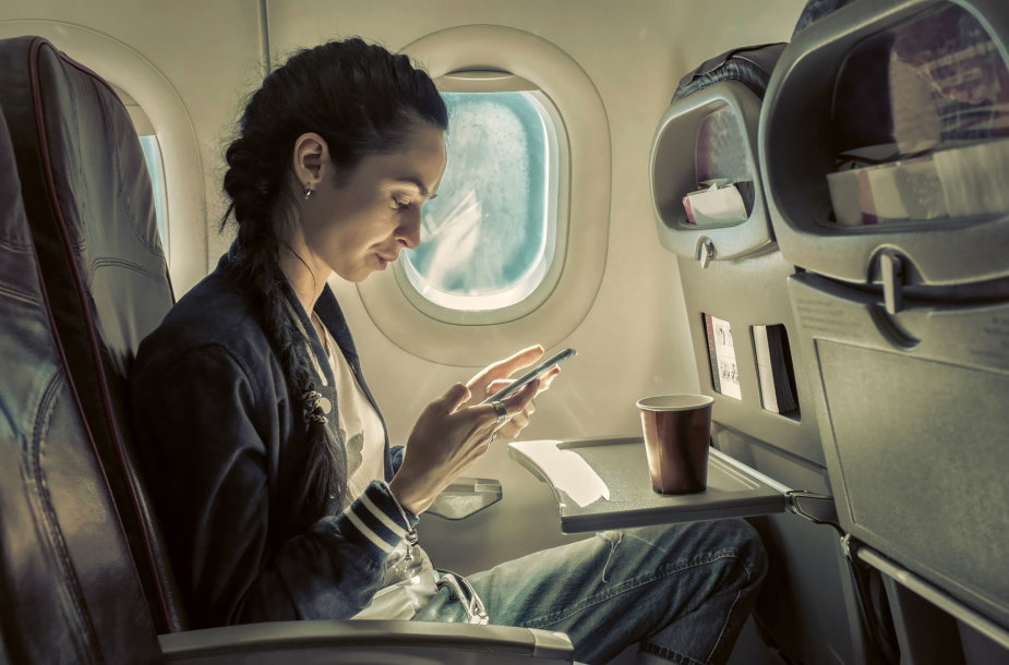 Mergina, kuri lėktuve naudojasi telefonu