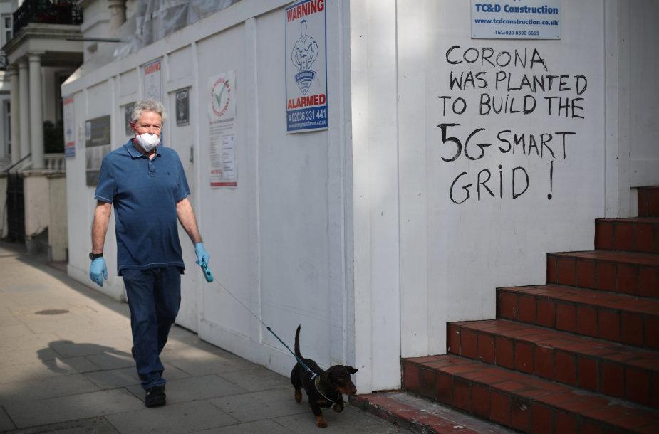 Vyras Londone greta sienos su užrašu skelbiančiu esą COVID-19 pandemija buvo pradėta 5G ryšio tinklui išplėsti