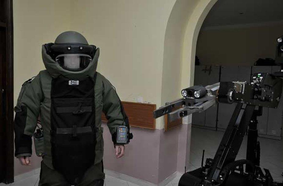 """Apsauginį kostiumą apsivilkęs išminuotojas ir jo pagalbininkas robotas """"Teodoras"""""""