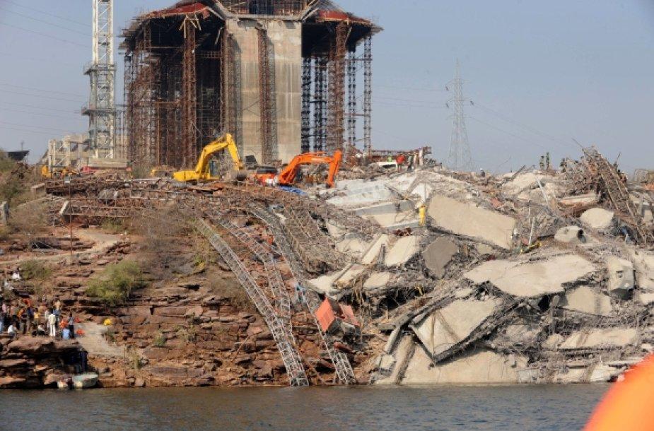 Indijos gelbėtojai po tilto griuvėsiais ir vandenyje ieško nelaimės aukų.