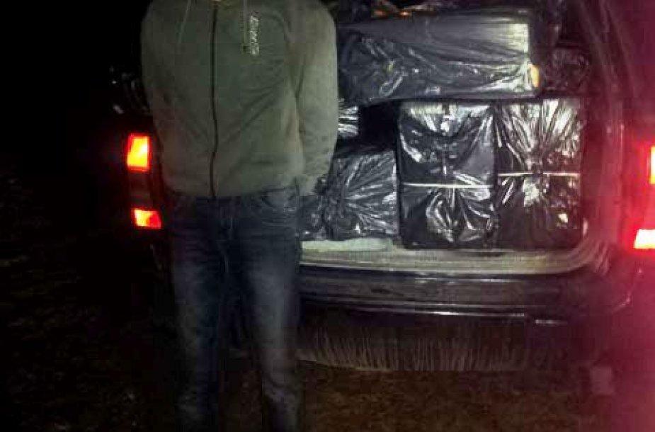 Kontrabandines cigaretes vežęs vyras prie automobilio