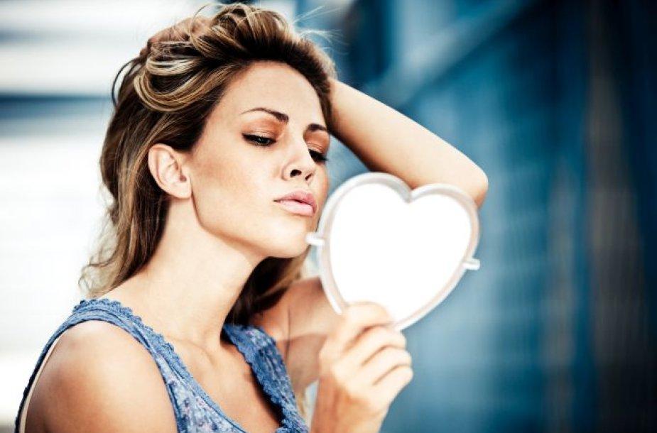 Moteris, žvelgianti į veidrodį