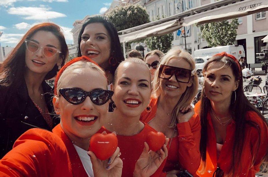 Moterys, pasipuošusios raudonai