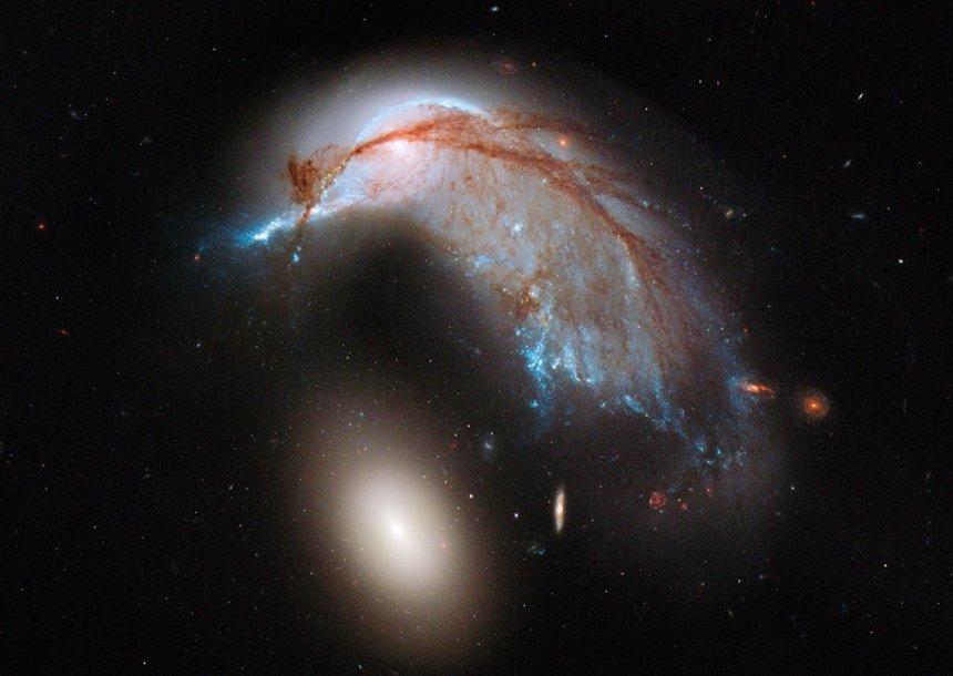 """Kosmoso platybėse neprasilenkė spiralinė galaktika """"NGC 2936"""" ir jos elipsinė kompanionė """"NGC 2937"""" (šviesi sritis apačioje)"""