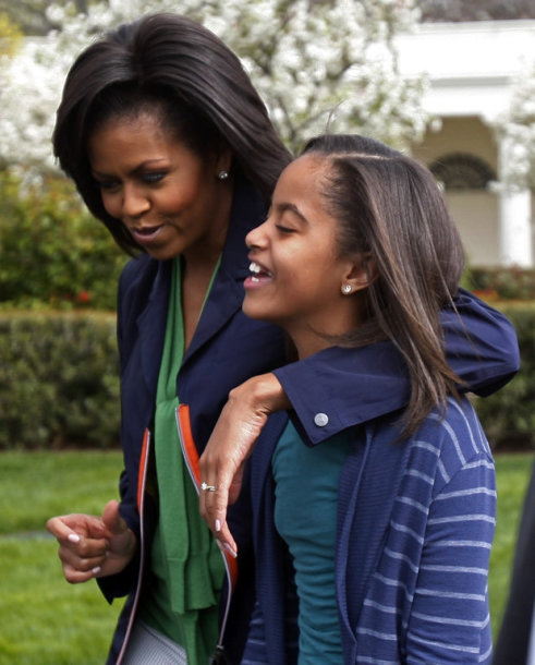 U.S. first lady Michelle Obama walks with her daughter Malia during the Annual Easter Egg Roll on the South Lawn at the White House in Washington, April 13, 2009. REUTERS/Jim Young (UNITED STATES POLITICS)